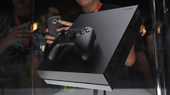 Gamers look at the new Microsoft Xbox One X during