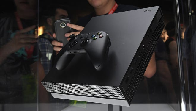 Gamers look at the new Microsoft Xbox One X during the Electronic Entertainment Expo in June.