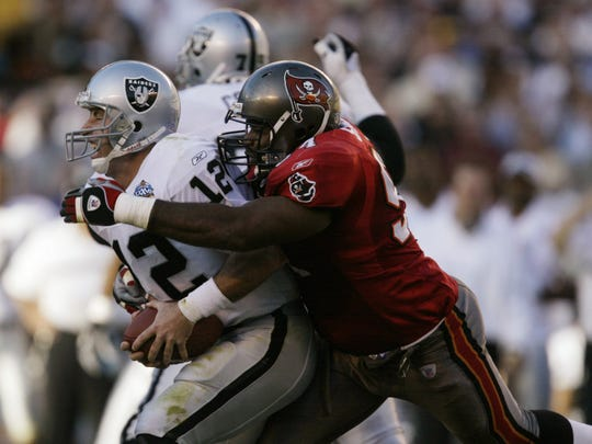 Tampa Bay Buccaneer Greg Spires, right, sacks Oakland Raiders quarterback Rich Gannon during the first quarter of Super Bowl XXXVII in San Diego, Sunday, Jan. 26, 2003. The third down sack by the Mariner High graduate left the Raiders in a fourth down punting situation.