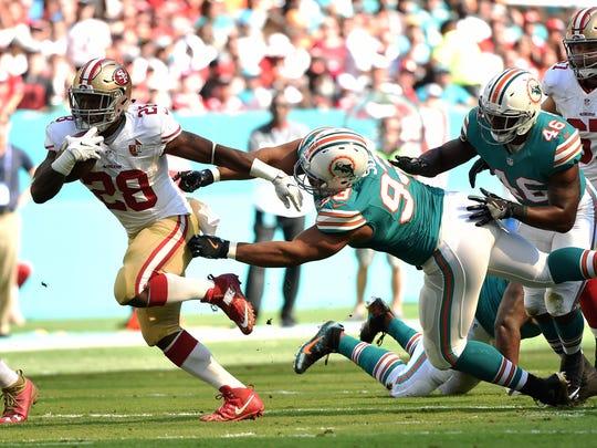 Nov 27, 2016; Miami Gardens, FL, USA; San Francisco 49ers running back Carlos Hyde (28) runs past Miami Dolphins defensive tackle Ndamukong Suh (93) during the first half at Hard Rock Stadium. Mandatory Credit: Steve Mitchell-USA TODAY Sports