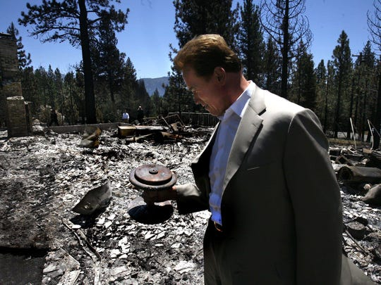 California Gov. Arnold Schwarzenegger curls a dumbbell that was found in the remains of a home that was destroyed by the Angora wildfire near South Lake Tahoe, Calif., Wednesday, June 27, 2007.