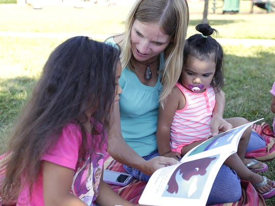 Pier Elementary School teacher Lisa Bebow reads to kids at Picnic and Pages. Held at Maplewood Commons apartment complex in Fond du Lac, the program promotes literacy and keep kids connected to school during summer vacation.