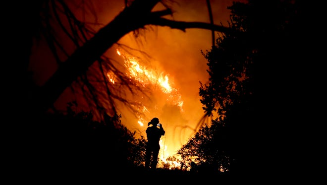 A firefighter takes a cell phone picture during a wildfire Saturday, Dec. 16, 2017, in Montecito, Calif. The so-called Thomas Fire is now the third-largest in California history.