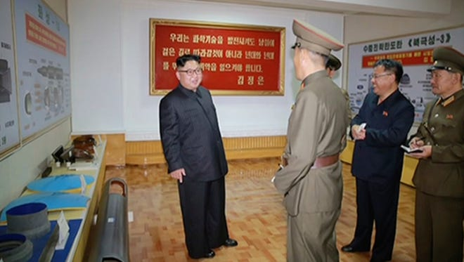 """In this image made from video of a news bulletin aired by North Korea's KRT on Wednesday, Aug. 23, 2017, leader Kim Jong Un visits the Chemical Material Institute of Academy of Defense Science at an undisclosed location in North Korea. North Korea's state media released photos that appear to show concept diagrams of the missiles hanging on a wall behind leader Kim Jong Un, one showing a diagram for a missile called """"Pukguksong-3."""""""