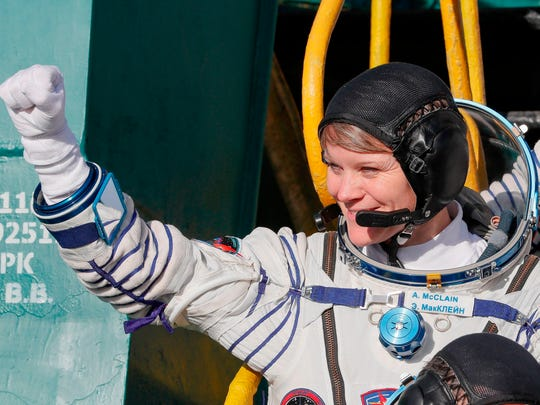 NASA astronaut Anne McClain gestures as she boards the Soyuz MS-11 spacecraft shortly before launch at the Russian-leased Baikonur cosmodrome in Kazakhstan on Dec. 3, 2018.