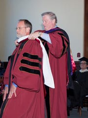 President Thrasher hoods Still, presenting him with his honorary degree.