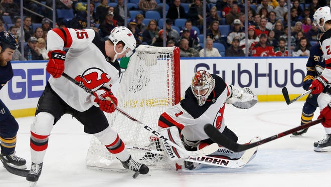 New Jersey Devils defenseman Mirco Mueller (25) tries to clear the puck after a save by goaltender Keith Kinkaid (1) against the Buffalo Sabres during the second period at KeyBank Center.