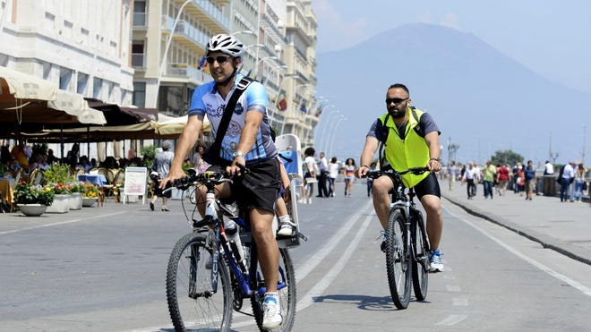 """Luca Simeone, founder of bike-sharing start up called """"bike tour Napoli,"""" left, pedals along a cyclists' path in Naples, Italy. In the background is Mt. Vesuvius."""
