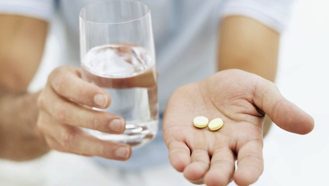 Drinking a half-glass of warm water after ? and before ? taking aspirin will help the pills dissolve faster.  Getty Images close-up of a person holding pills and a glass of water