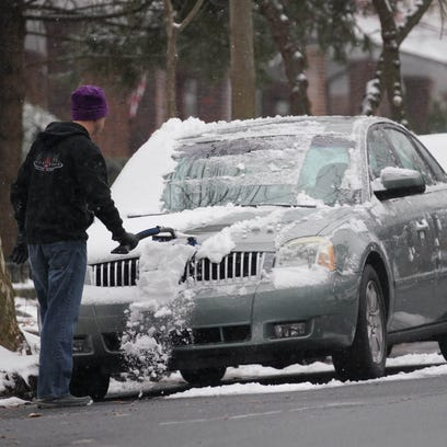 A motorist removes snow off his vehicle along Delaware