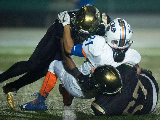 Campbell County's Riley Wallace is tackled by Catholic's