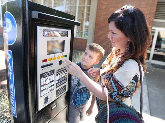 Sherri Clark of Salem and her son, Linus, 8, use one of the new parking pay stations on Wednesday, Sept. 14, 2016, along Chemeketa Street in downtown Salem.