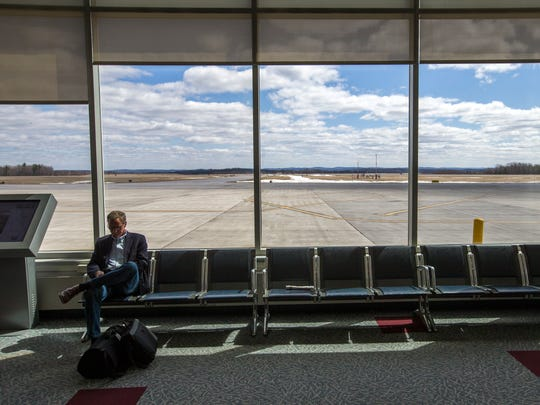 A man waits to board his flight in the terminal at