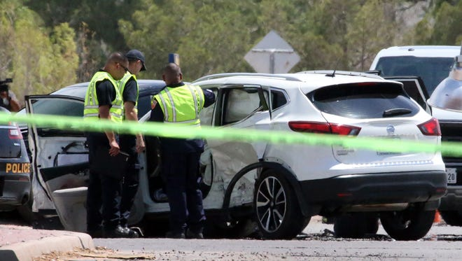 El Paso police investigators look at a white SUV, one of at least three vehicles involved in a fatal traffic accident at Pan American Drive and South Americas Avenue on Thursday in El Paso's Lower Valley.