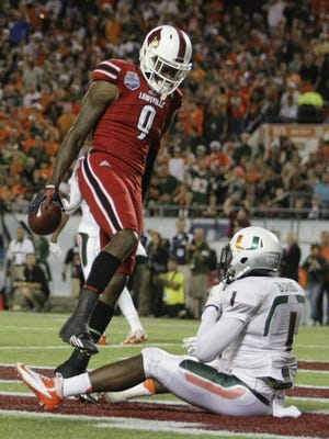 Louisville's Devante Parker stands over Miami's Artie Burns after scoring the Cards first touchdown in the Russell Athletic Bowl in Orlando.