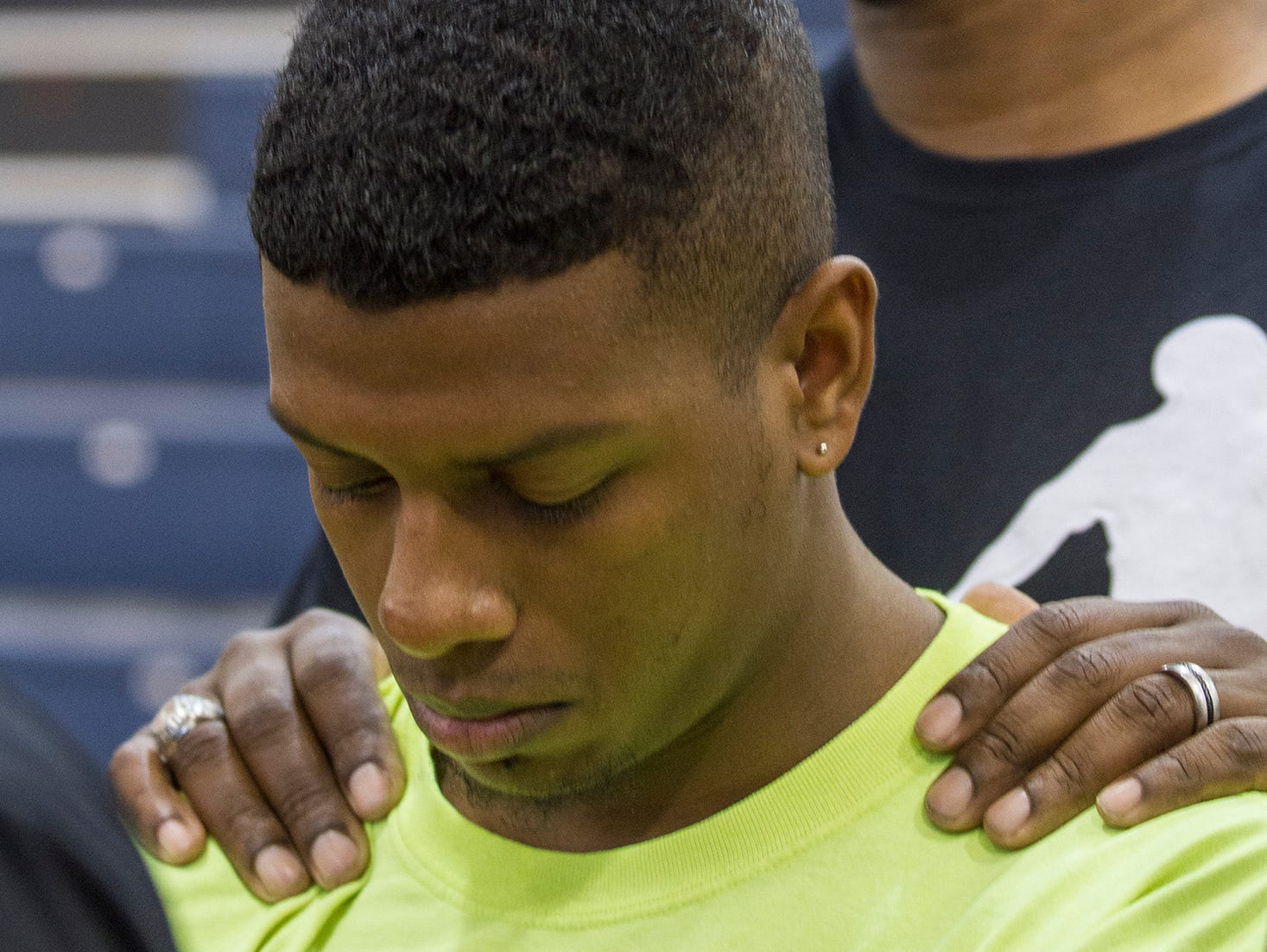 Alex Debnam, 19, a friend and former teammate of Stef'An Strawder, is comforted by Bernard Edwards, a parent of one of his teammates, during a press conference at the Lehigh Senior High School gym Monday afternoon. School administration, parents and teammates were in hand to share their feelings about the loss of Strawder during a shooting Monday morning in Fort Myers.
