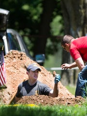 Pennsylvania State Police Cpl. Nathan Trate (center) looks for evidence in the grave where investigators exhumed the body of a Jane Doe in hopes of solving a cold case from 1973 at Mt. Lebanon Cemetery on Tuesday, May 31, 2016. Investigators are hoping to identify a woman who was found dead in the woods along Moonshine Road in Union Township on Oct. 10, 1973 and was buried in the Lebanon cemetery.