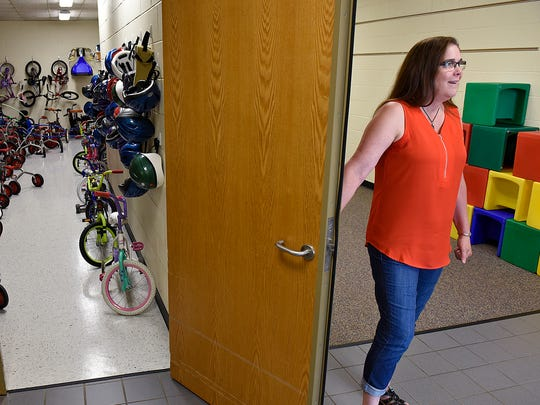 Early Childhood Education Director Alicia Jepsen opens the door to the storage area for the program's many bicycles June 5 at Colts Academy in St. Joseph. The bicycles were recovered and refurbished after the fire that destroyed Roosevelt Education Center last year.