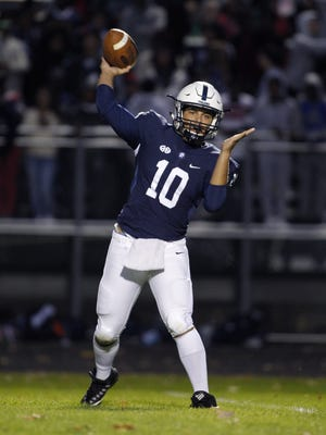 East Lansing quarterback Connor Charamella throws a pass against Holt on Friday, Sept. 29, 2017. Charamella ranks among the top passers in the Lansing area this fall.