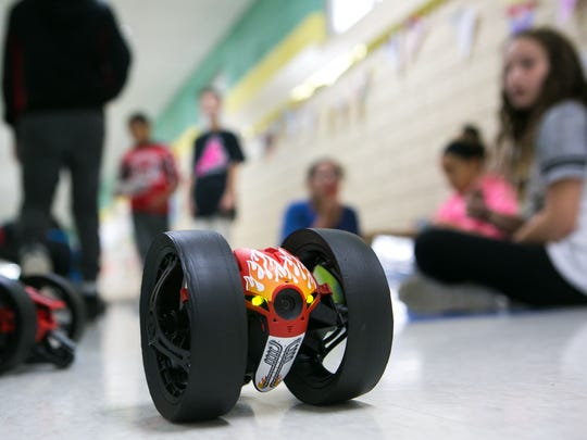 Lisa Mims's fifth-grade students at Pleasantville Elementary control ground and aerial drones on the hallway of their classroom.