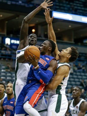 The Bucks' Thon Maker and Malcolm Brogdon, right, defend Pistons guard Reggie Jackson during the first half on Friday, Oct. 13, 2017, in Milwaukee.