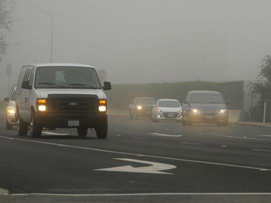 Looking west along Noble Avenue at Demaree Street, fog blankets Visalia Friday morning. Visibility was down to an eighth of a mile or less in places.
