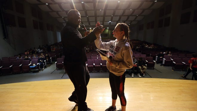 Former New York Giant Lee Rouson gives a high-five to 8th grader Haley Asbury after she performed during a new program called 'The Hook' at Mount Olive Middle School.  Rouson, an activities coordinator in the Mt. Olive school district, judged and organized the school program. March 4, 2016. Mt. Olive, N.J.