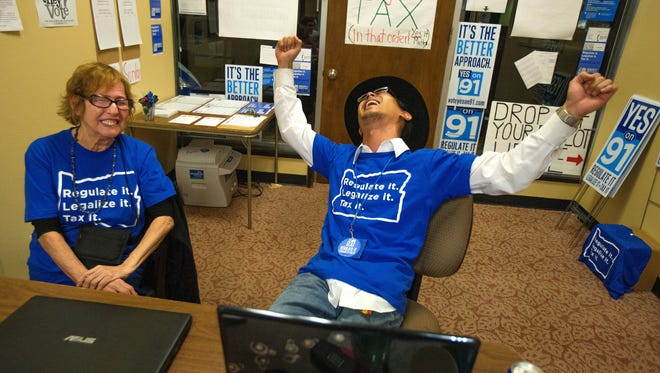 Matthew Yook, a field organizer for Measure 91, celebrates early returns that favor the Oregon Legalized Marijuana Initiative with Elvy Musikka, a medical marijuana recipient, at their downtown headquarters in Eugene, Ore., on Tuesday, Nov. 4, 2014. (AP Photo/The Register-Guard, Brian Davies)