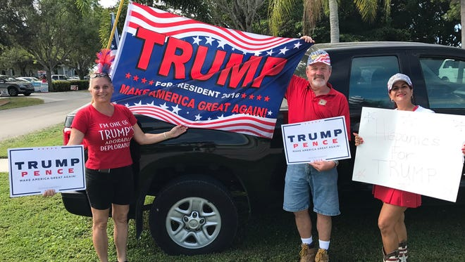 (Left to right) Marco Island residents Dale Danek Downey, Jimmy Downey and Yvette Benarroch show support for GOP presidential candidate Donald Trump outside of Precinct 193 on Election Day, Tuesday Nov. 8. The trio visited various places around the island and said most of the feedback they received was positive.