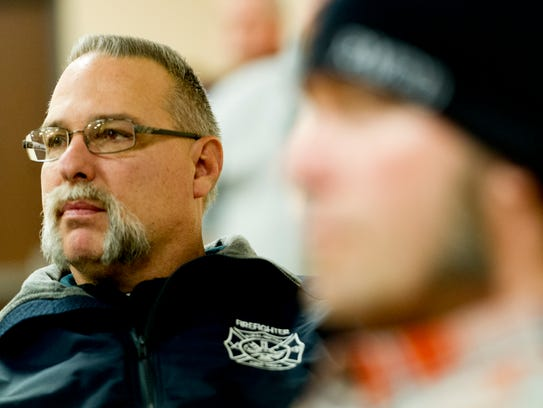 Rural Metro firefighter Lee Raypurn listens during