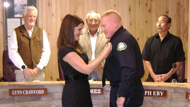 Cecily Hooker pins the Ruidoso police chief''s badge on her husband, Darren Hooker, as village councilors Lynn Crawford, Joe Gomez and Joseph Eby watch with others who crowded into the council chambers to see Hooker take his oath of office Tuesday.
