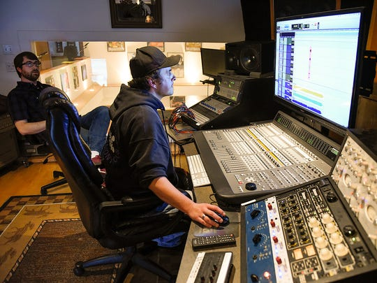 Dirty Mercury band members Brandon Surerus, left, watches and listens as recording engineer Thomas Cabot records a guitar track for the band's next album Wednesday, April 27, at Rockhouse Productions in St. Joseph.