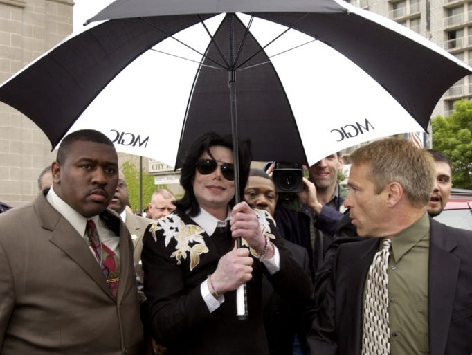 Michael Jackson returned to his hometown of Gary in June 11, 2003, for the first time since his childhood. After a press conference inside the Gary City Hall (background left)) where he was given a key to the city he walked to his limousine then emerged and signed some autographs for fans who packed the street in front of City Hall. Gary school district officials are now planning to name a school in his honor.