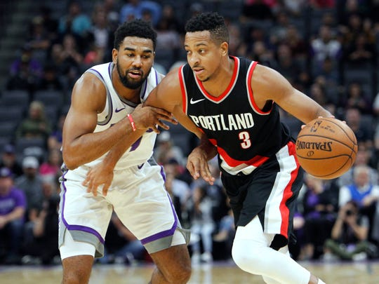 FILE - In this Oct. 9, 2017, file photo, Portland Trail Blazers guard CJ McCollum, right, is fouled by Sacramento Kings defender Matt Jones during the first half of an NBA preseason basketball game in Sacramento, Calif. The season opener for the Trail Blazers has come with an unexpected twist--The absence of starter McCollum, who is suspended for their season opener at Phoenix on Wednesday, Oct. 18, 2017. (AP Photo/Steve Yeater, File)