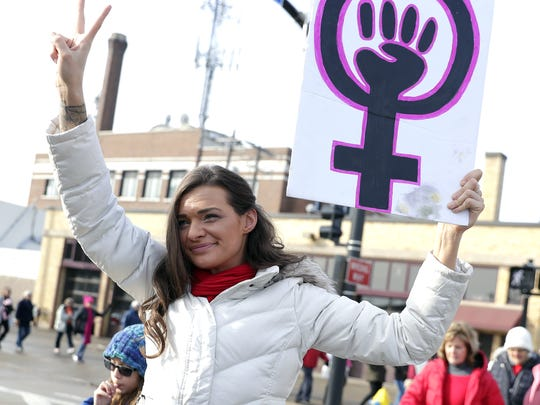 Cassandra Erickson of De Pere walks with a sign during the Women's March held Saturday in Green Bay.