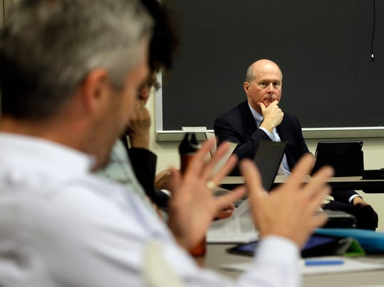In this photo taken Thursday, May 1, 2014 University of North Carolina Executive Vice Chancellor and Provost James W. Dean Jr., right, listens during a Student-Athlete Academic Initiatives Working Group in Chapel Hill, N.C. After three years of scandal at North Carolina, school officials have spent the past school year conducting a comprehensive review of its academic support programs for athletes. (AP Photo/Gerry Broome)