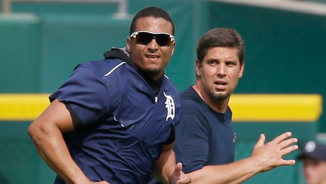 Detroit Tigers designated hitter Victor Martinez runs sprints with Chris McDonald, the team strength and conditioning coach, during batting practice June 10, 2015, in Detroit.