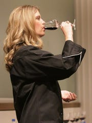Kohler head chocolatier Anette Right Defendi samples fine wine while holding chocolate in her hand during the Kohler Food and Wine Experience, Friday, October 20, 2017, in Kohler, Wis.