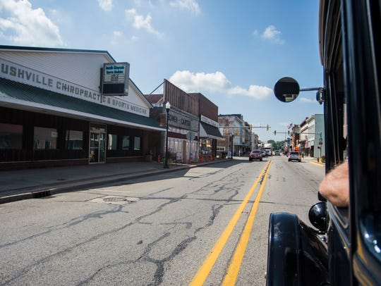 A Ford Model T travels down Main Street in downtown
