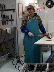 Ed Fee prepares to dress a 5-pound salmon for a customer.