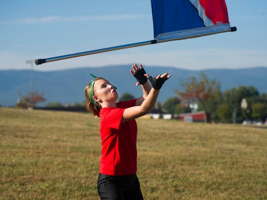 Kayla Abshire, a junior at Riverheads and member of the color guard, warms up before performing at the Blast in the Draft marching band competition at Stuarts Draft High School on Saturday, Sept. 27, 2014.