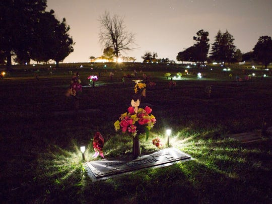 Lights illuminate headstones at Oak Lawn Memory Gardens in Staunton early in the morning on Friday, Aug. 22, 2014.