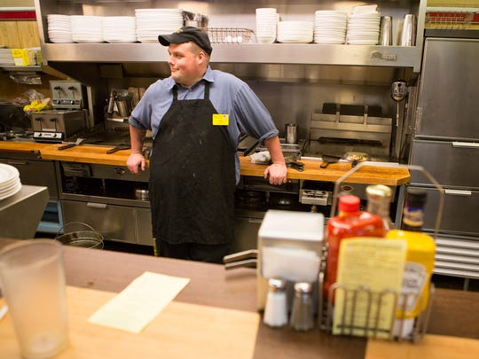 Andrew Laugherty, an employee at Waffle House, stands behind the counter during his night shift early in the morning on Friday, Aug. 22, 2014.