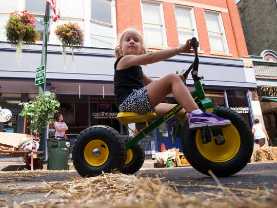 Quinn White rides a tricycle along a closed portion of West Beverley Strett during the Staunton Jams street concert on Saturday, Aug. 30, 2014.