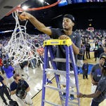 Duke's Quinn Cook cuts down the net after a college basketball regional final game against Gonzaga in the NCAA Tournament Sunday.