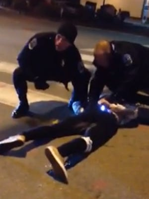 This still made from a video recorded by a bystander early Sunday morning shows Burlington police officers struggling with Shane Langevin, 20, of Winooski.