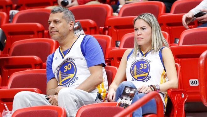 Golden State Warriors fans look on during warmups before the start of an NBA basketball game between the Miami Heat and the Warriors.