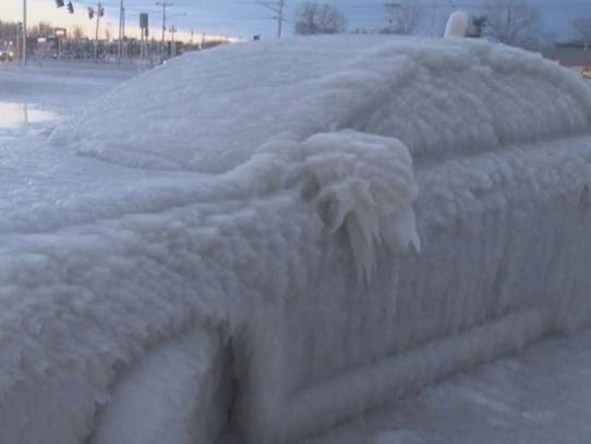 Car covered in ice on one side in New York.