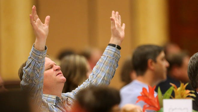 Adam Swanson raises his hands in praise as the North Boulevard Praise Team sings during the Mayors Prayer Breakfast, on Thursday, May 5, 2016.