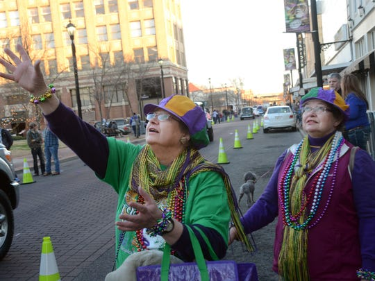 Christine Craig (left) and her twin sister, Diane Raineri, look for throws Friday during the Classic Cars & College Cheerleaders Parade in downtown Alexandria. Raineri and her husband John came in for the Alexandria Mardi Gras celebrations from Troy, Michigan. They come every other year for the festivities. Craig said she bought her sister the hat she is wearing.